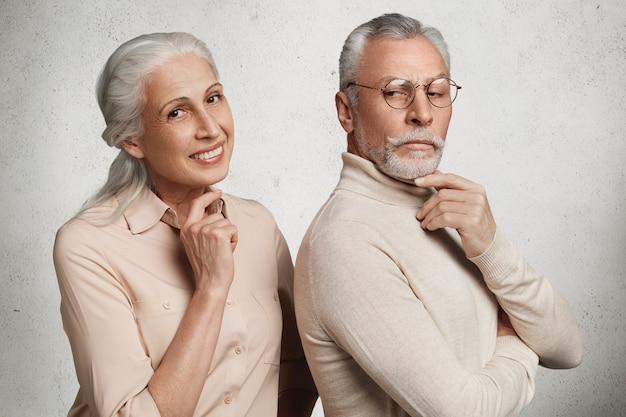 Los pares mayores en el amor se colocan cerca el uno del otro. anciana sonriente con expresión complacida