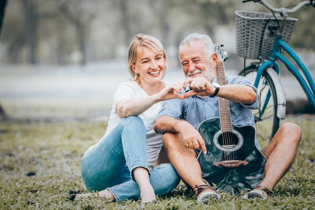 Los pares mayores en amor muestran el icono en forma de corazón hecho a mano que se sienta en hierba en el parque