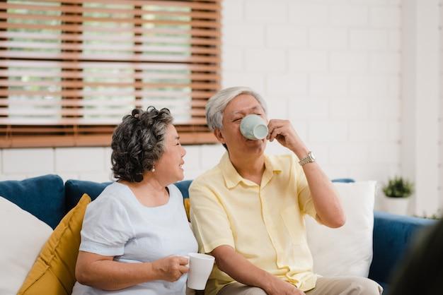 Los pares mayores asiáticos que beben el café caliente y que hablan juntos en sala de estar en casa, los pares disfrutan del momento del amor mientras que mienten en el sofá cuando está relajado en casa.