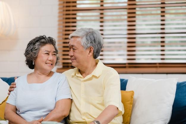 Los pares mayores asiáticos que llevan a cabo sus manos mientras que toman juntos en sala de estar, los pares que sienten parte feliz y se apoyan que mienten en el sofá en casa.
