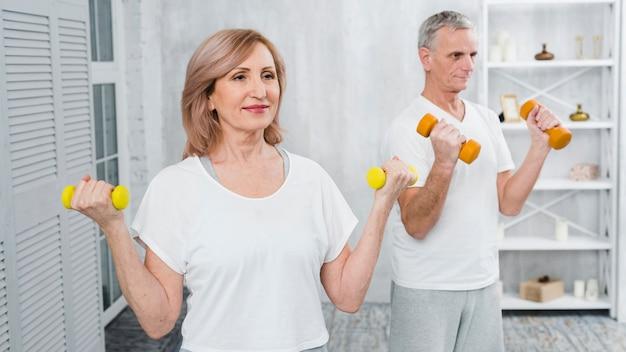 Pares mayores felices que ejercitan usando pesas de gimnasia
