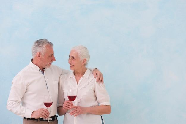 Pares mayores felices que miran uno a que sostiene la copa de vino contra fondo azul