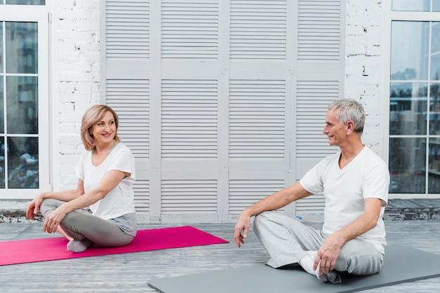 Pares mayores felices que se sientan en la estera de la yoga que mira uno a