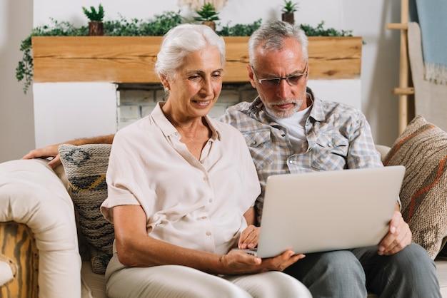 Pares mayores felices que se sientan en el sofá que mira el ordenador portátil