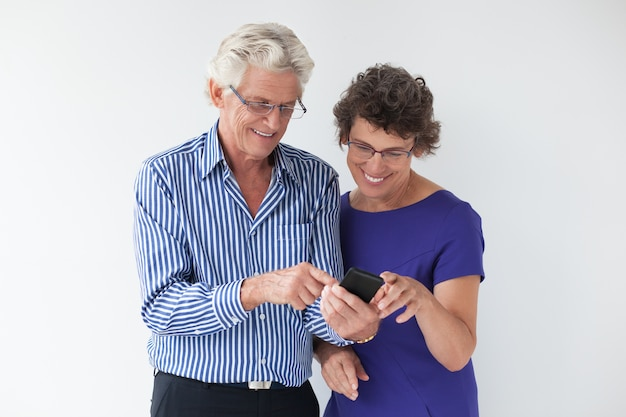 Pares mayores felices usando smartphone