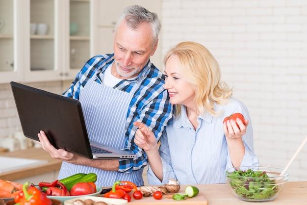 Pares mayores que miran el ordenador portátil mientras que prepara la ensalada vegetal en la tabla de madera