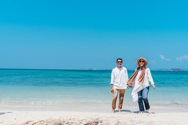 Pares musulmanes sonrientes de los jóvenes que llevan a cabo las manos en la playa en día de vacaciones.