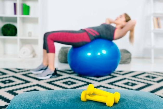 Pares de pesas de gimnasia amarillas delante de la mujer que ejercita en la bola azul de los pilates