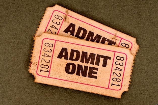 Los pares de rasgado viejos admiten boletos de una película en un fondo marrón.