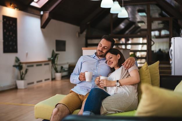 Los pares se relajan en casa con la taza de café y el sofá del sofá.