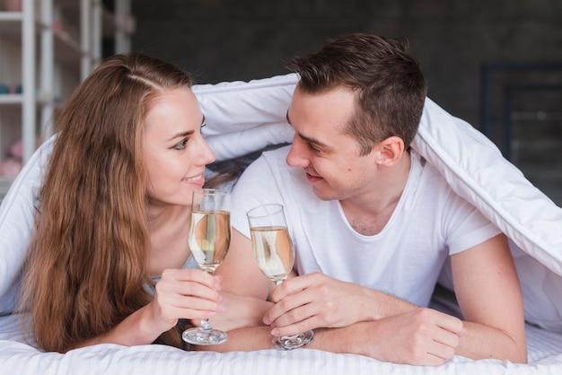 Pares sonrientes que mienten en cama debajo del edredón con los vidrios de la bebida