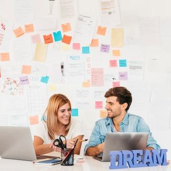 Pares sonrientes que se sientan en el escritorio con las computadoras portátiles contra la pared con las notas