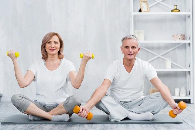 Pares sonrientes que se sientan en la estera de la yoga que ejercita con pesas de gimnasia
