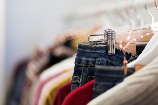 Párese con perchas de ropa en la tienda