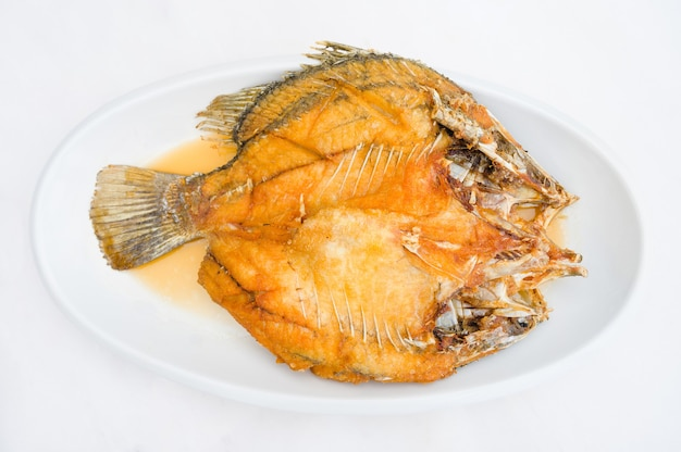 Pargo frito en plato blanco con salsa de pescado