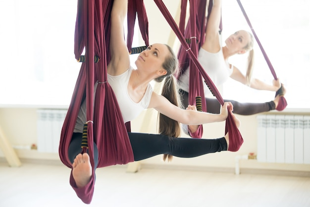 Parivrtta upavistha konasana yoga plantean en la hamaca