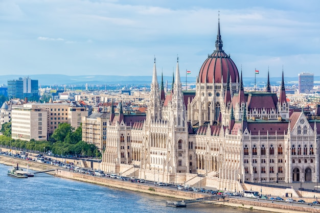El parlamento y la orilla del río en budapest hungría con barcos de turismo durante el día de verano con cielo azul y nubes