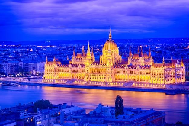 El parlamento y la orilla del río en budapest hungría durante la puesta del sol de la hora azul