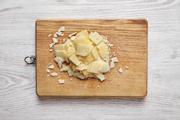 Parmesano en rodajas, aislado en un escritorio de madera sobre una mesa blanca