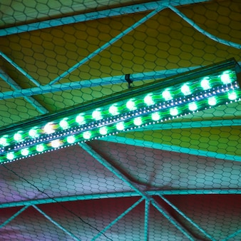 Parque de atracciones en la noche con luces verdes y azules