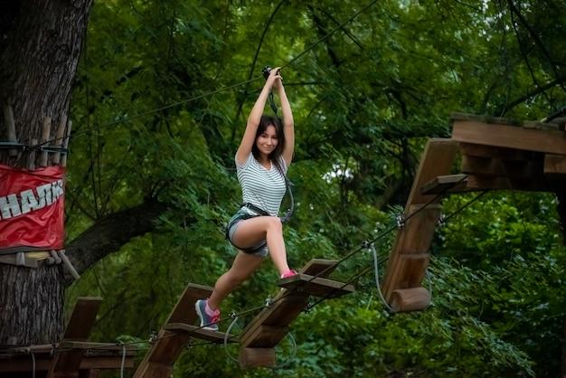 Parque de cuerdas, carrera de obstáculos, estilo de vida activo, hermosa chica practica deportes