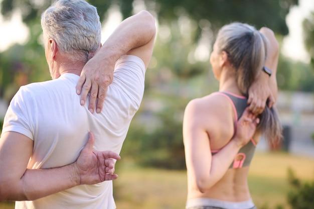 En el parque. un hombre y una mujer haciendo ejercicio en el parque.
