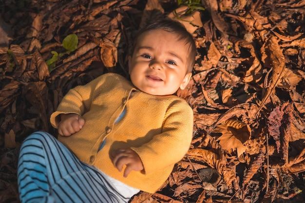 Parque en una puesta de sol de otoño, bebé de seis meses sonriendo acostado en las hojas de los árboles