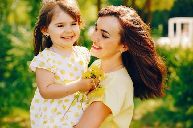 En un parque de verano cerca de árboles verdes, mamá camina vestida de amarillo y su pequeña niña bonita