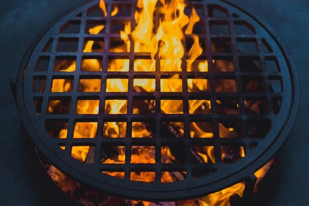 Parrilla de la barbacoa, primer plano. cocinando profesionalmente comida en un fuego abierto sobre una rejilla de hierro fundido.