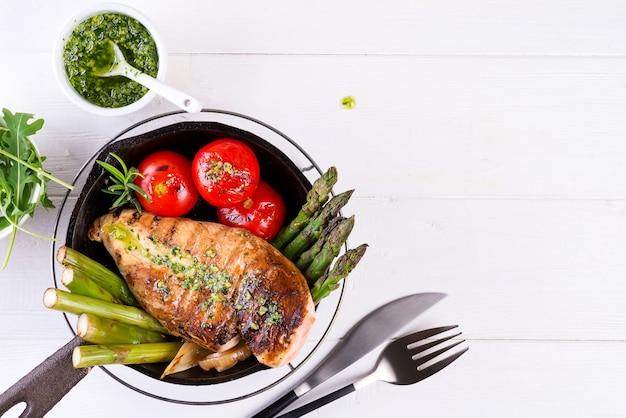 Parrilla de pechuga de pollo con verduras a la barbacoa y salsa de pesto en una sartén de hierro fundido en blanco