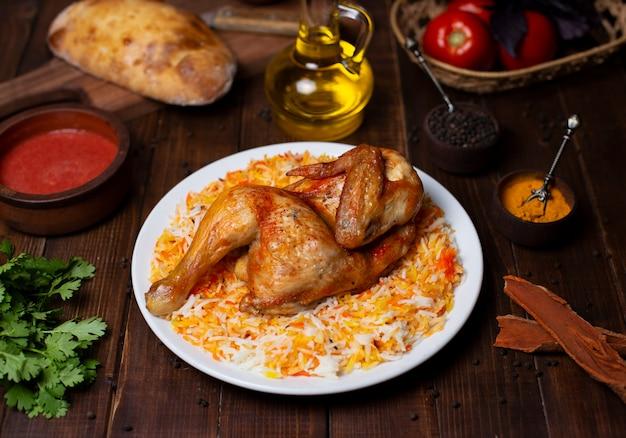 Parrilla de pollo entero servido con guarnición de arroz en plato blanco.