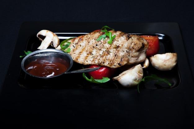 Parrilla de pollo en el plato con tomates y champiñones sobre un fondo oscuro