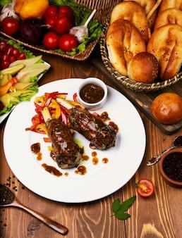 A la parrilla con salsa teriyaki cordero de ternera con pimiento asado en un plato blanco.