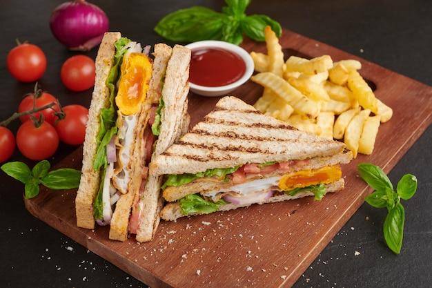 A la parrilla y sándwich con tocino, huevo frito, tomate y lechuga servido en tabla de cortar de madera