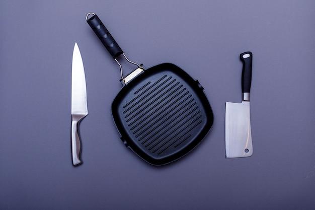 Parrilla vacía en la mesa de la cocina casera. cuchillos metálicos, parrilla y cuchilla. lay flat, diseño.