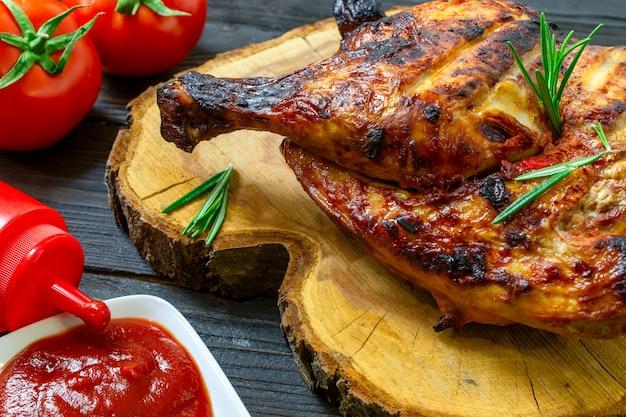 Parte al horno de sabroso pollo, con corteza de color marrón dorado, cocinado en barbacoa en la mesa de madera oscura.