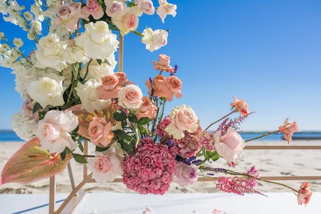 Parte del arco de boda decorado con flores frescas se encuentra en la orilla arenosa del río