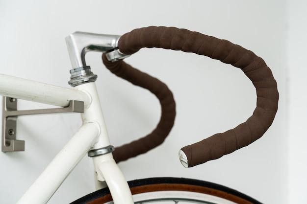 Parte de la bicicleta retro colgada en la pared blanca