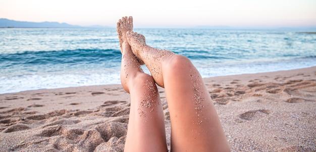 Parte del cuerpo. pies femeninos en la arena de la playa junto al mar de cerca.