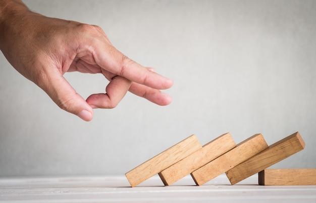 Parte del dedo humano empujar dominó de madera sobre la mesa