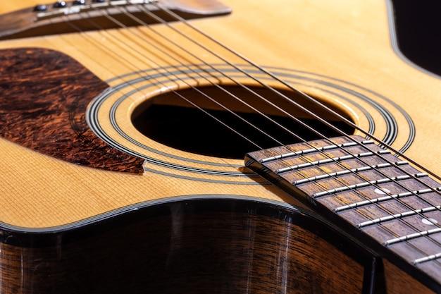 Parte de una guitarra acústica, diapasón de guitarra con cuerdas sobre un fondo negro.