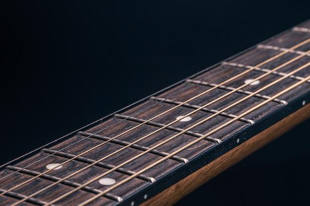 Parte de una guitarra acústica, diapasón de guitarra sobre un fondo negro.