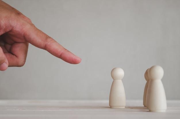 Parte de la mano humana apunta a la de muñecas de madera de la fila