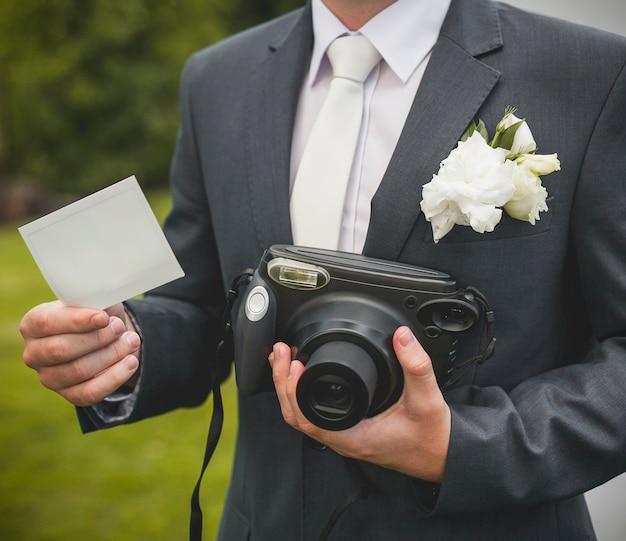 Parte del novio con cámara retro y tarjeta vacía
