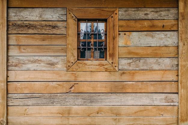 Parte de la pared de una casa de madera antigua con una pequeña ventana