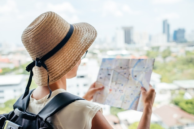 Parte posterior de la chica viajera buscando la dirección correcta en el mapa, viajando por asia