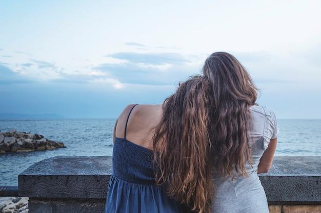 Parte posterior de la mujer apoyada en el hombro de un amigo mirando el mar