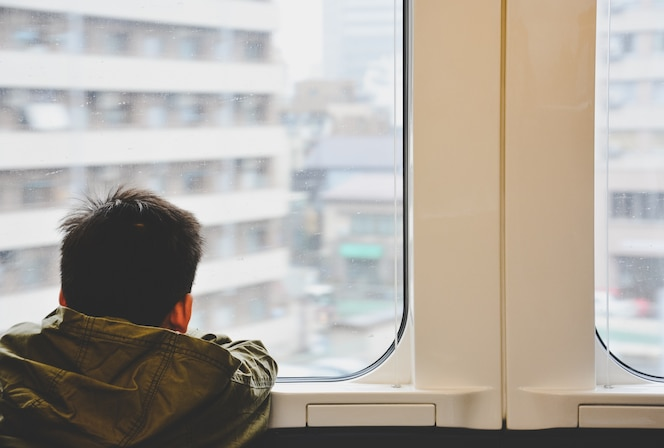 Parte posterior del niño pequeño que viaja en tren y mirando a través de la ventana de vidrio