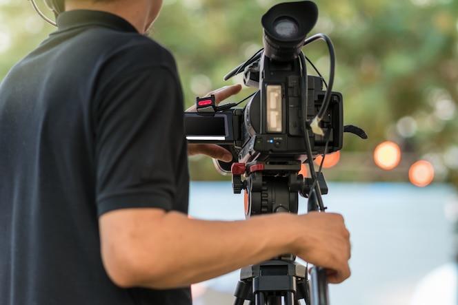 Parte posterior del video cameraman tomando fotografías en el equipo de producción de escenario, evento y seminario c