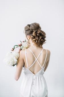 Parte posterior de la joven hermosa mujer con ramo de flores de peonía.